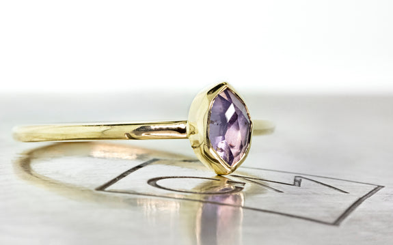 .77 carat hand cut purple sapphire in bezel setting in 14 karat yellow gold side view on Chinchar Maloney metal plate