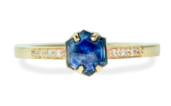 1.04 carat hand cut vibrant blue sapphire with 3 pave diamonds on each side set in yellow gold front view on white background