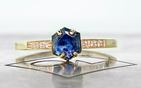 1.04 carat hand cut vibrant blue sapphire with 3 pave diamonds on each side set in yellow gold front view on Chinchar Maloney metal plate  on white background