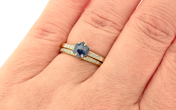 1.04 carat hand cut vibrant blue sapphire with 3 pave diamonds on each side set in yellow gold paired with yellow gold band with pave diamonds top view on finger