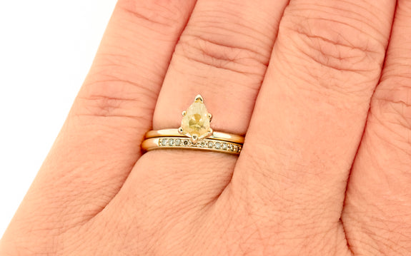 .68 carat light champagne diamond ring set in yellow gold paired with yellow gold band with pave diamonds top view on finger