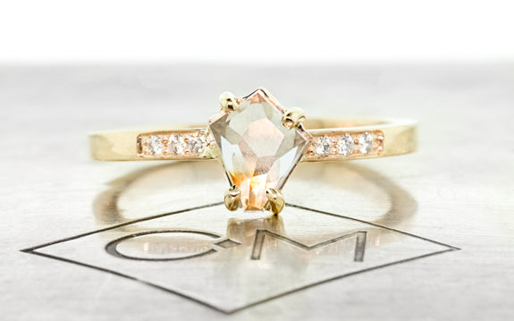 .95 carat Hand Cut sea foam and peach Montana sapphire set in 14 karat yellow gold with three pave diamonds on each side front view on Chinchar Maloney metal plate on white background
