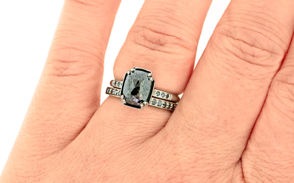 Maroa ring with 1.5 carat black diamond with three black pave diamonds on each side set in 14 karat white gold paired with 14 karat white gold band with black pave diamonds top view on finger