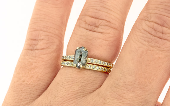 1 carat salt and pepper diamond with six pave diamonds on each side set in 14 karat yellow gold paired with 14 karat yellow gold band with pave diamonds top view on finger on white background