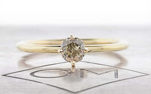 .50 carat sparkling champagne diamond set in 14 karat yellow gold front view on Chinchar Maloney metal plate on white background