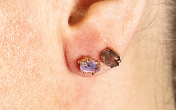 Pair of hand-cut violet Montana sapphire earrings in rose gold front view together on ear
