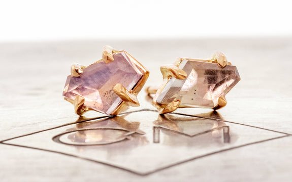 Pair of hand-cut violet Montana sapphire earrings in rose gold front view on Chinchar Maloney metal plate