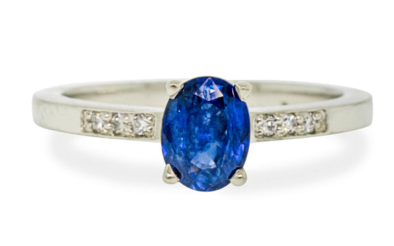 .88 carat blue sapphire with three white pave diamonds on each side front view on white background