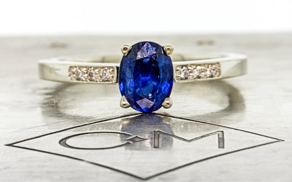 .88 carat blue sapphire with three white pave diamonds on each side front view on Chinchar Maloney metal plate