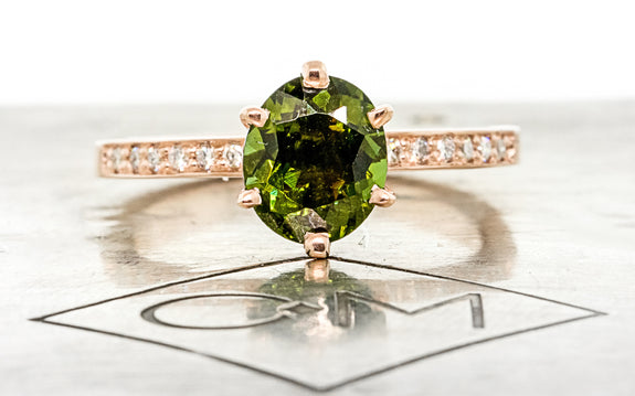 1.37 carat green tourmaline with six pave diamonds on each side set in 14 karat rose gold front view on Chinchar Maloney metal plate