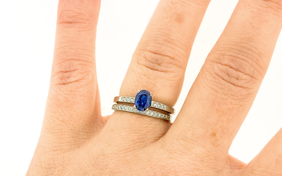 .88 carat blue sapphire with three white pave diamonds on each side paired with 16 white diamond wedding band top view on finger