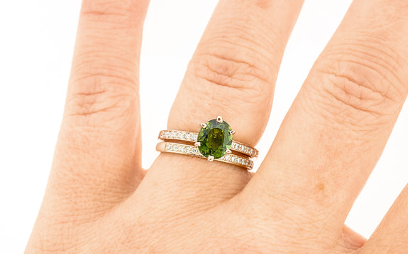 1.37 carat green tourmaline with six pave diamonds on each side set in 14 karat rose gold paired with 16 diamond wedding band in 14 karat rose gold top view on finger