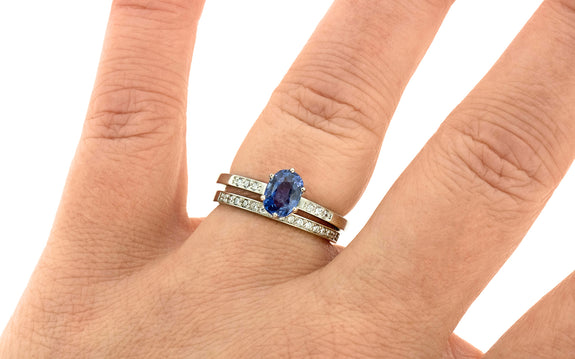 1.15 carat waterfall blue sapphire set in 14 karat white gold with three white pave diamonds on each side paired with sixteen diamond wedding band in white gold top view on finger
