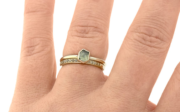 .72 carat hand cut dusted olive green Montana sapphire bezel set in 14 karat yellow gold paired with wedding band in 14 karat yellow gold with 16 gray pavé diamonds top view on finger