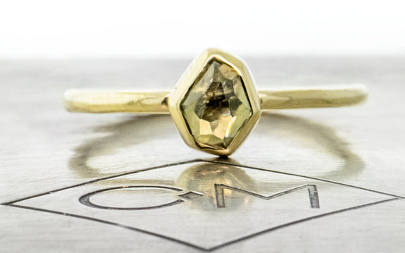 .78 carat hand cut dusted olive green Montana sapphire ring bezel set in 14 karat yellow gold front view on Chinchar Maloney metal plate