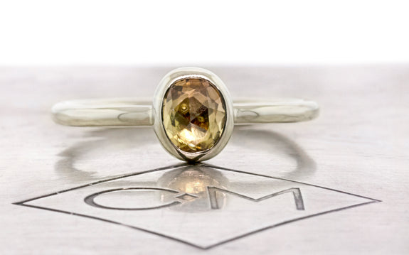 .72 carat hand cut tupelo honey sapphire ring bezel set in 14 karat white gold front view on Chinchar Maloney metal plate