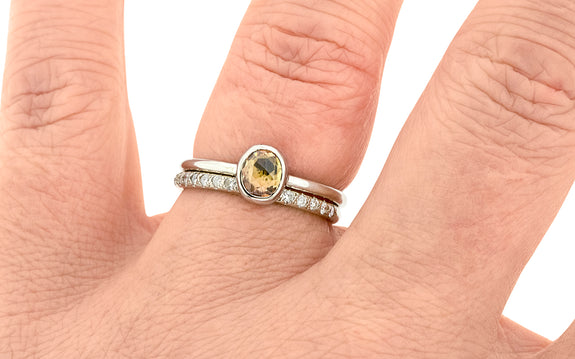 .72 carat hand cut tupelo honey sapphire ring bezel set in 14 karat white gold paired with 14 karat round white gold wedding band with 16 white pavé diamonds top view on finger