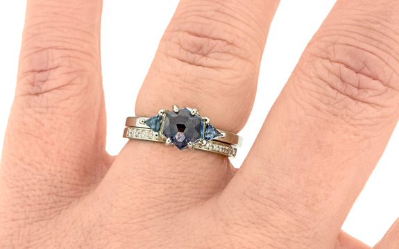 1.63 carat windy blue Montana sapphire ring set in 14 karat white gold with one trillion cut blue sapphire on each shoulder paired with 14 karat white gold wedding band with 16 white diamonds top view on finger