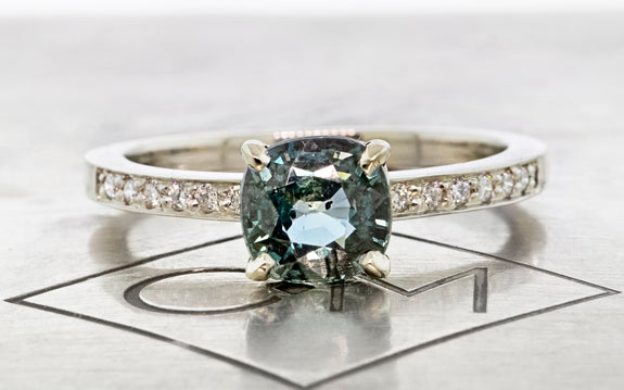 1.55 carat parkwater teal sapphire ring in 14 karat white gold with six white pave diamonds on each shoulder front view on Chinchar Maloney metal plate