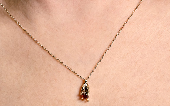 14 karat yellow gold heart in hand pendant with 5mm garnet on 14 karat yellow gold 18 inch chain front view on neck
