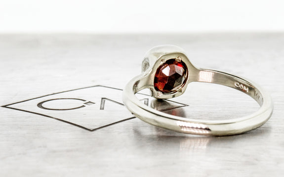 Diamond & Garnet Skull Ring side view on logo