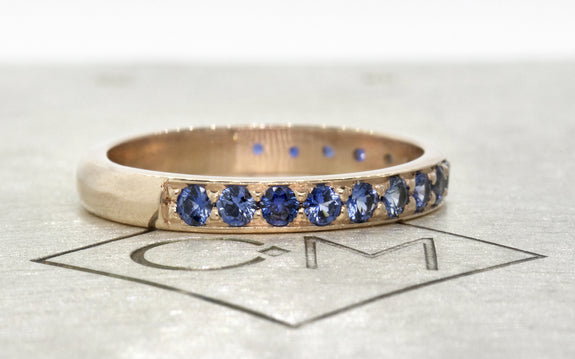 Wedding Band with 16 Blue 2mm Sapphires side view on logo