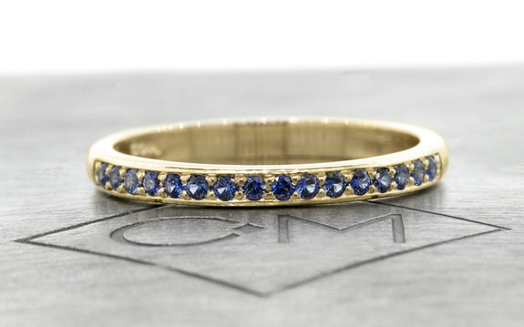 Wedding Band with 16 Blue Sapphires in white gold front view on logo