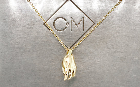 14 karat yellow gold hamsa hand pendant with 2mm white diamond on 14 karat yellow gold 18 inch chain back view on Chinchar Maloney metal plate