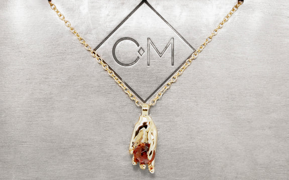 14 karat yellow gold heart in hand pendant with 5mm garnet on 14 karat yellow gold 18 inch chain front view on Chinchar Maloney plate