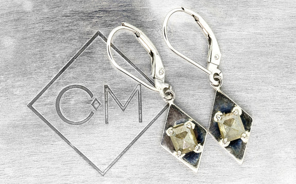 .21 champagne diamond earrings alongside logo