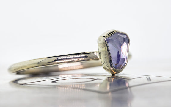 .76 carat hand cut lavender blue Montana sapphire bezel set in white gold side view on Chinchar Maloney metal plate on white background