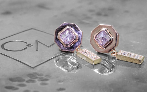 .38ct pink/purple diamond earrings front view on logo