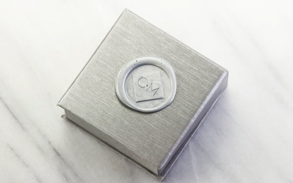 silver Chinchar Maloney necklace box with sealing wax logo on white background