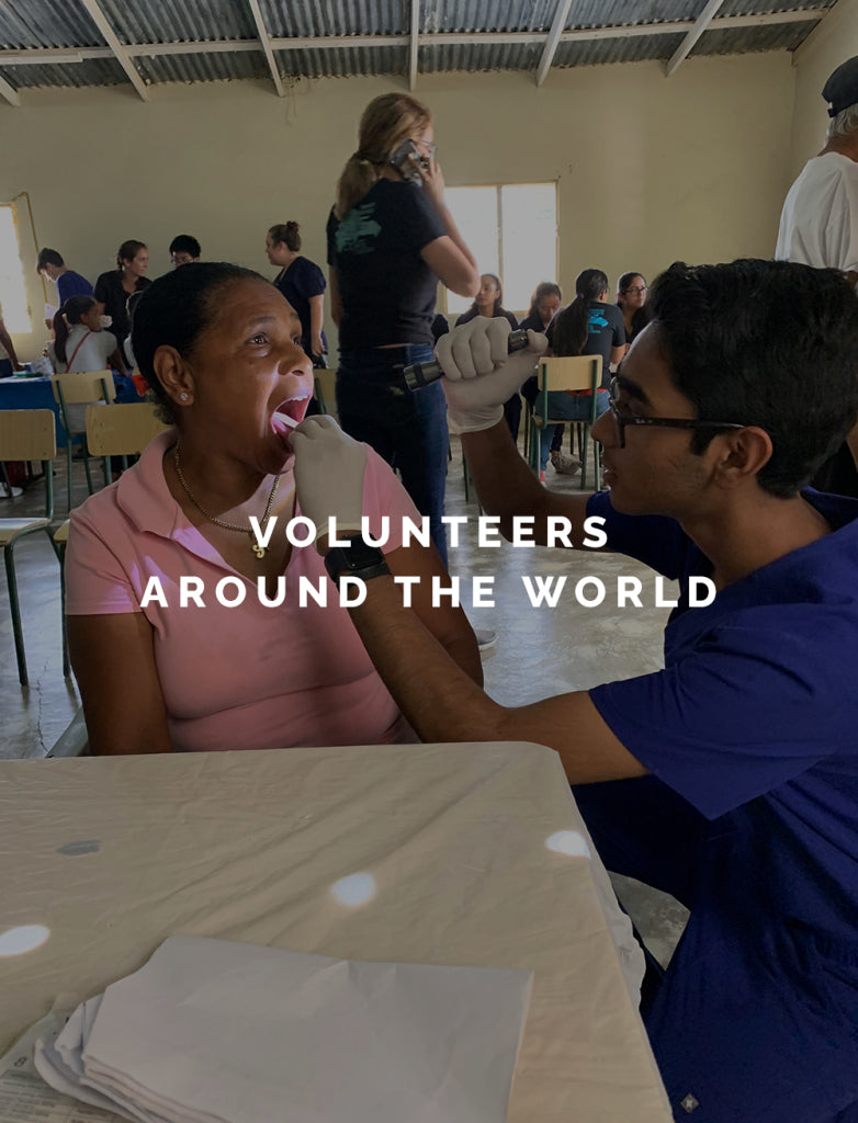 A man in scrubs checking a womans throat with text reading Volunteers Around The World