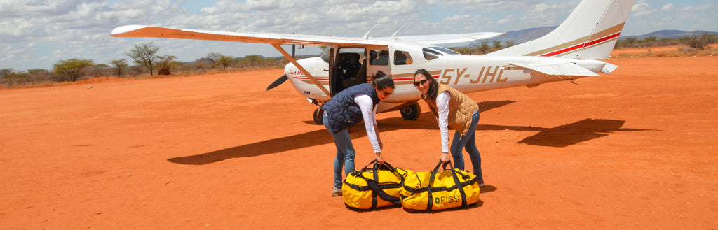 Picture of Heather Hasson and Trina Spear by a plane loading Threads for Threads supplies.