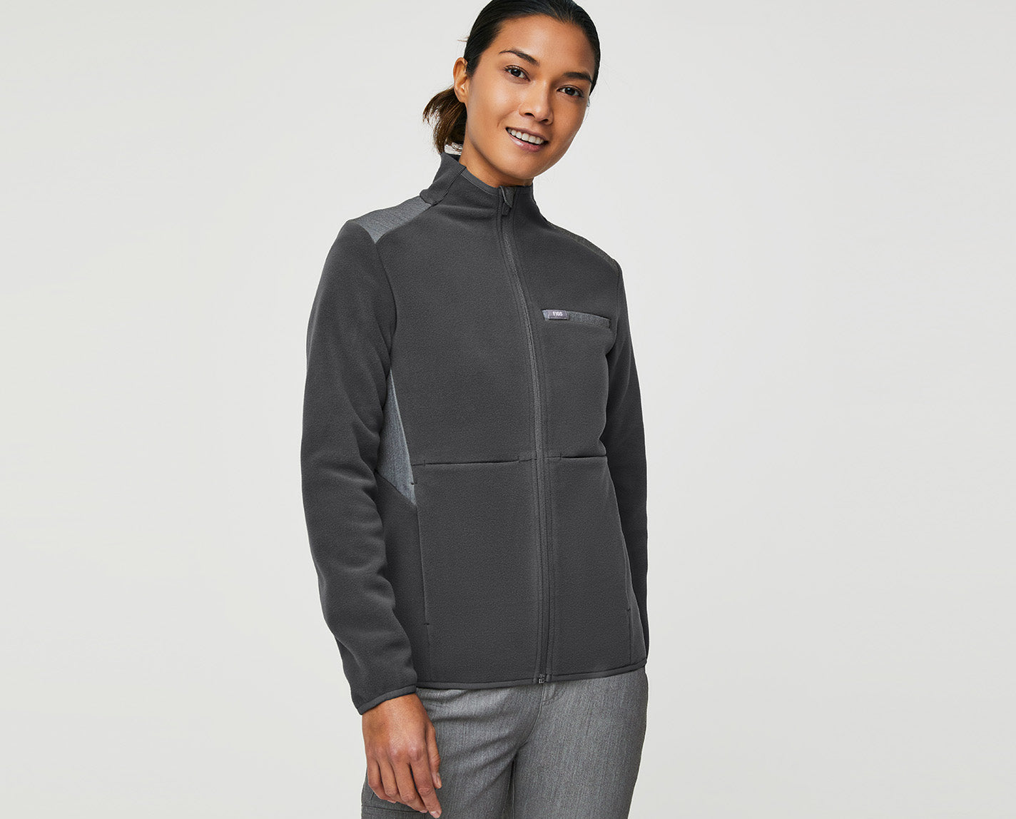 Our On-Shift Fleece Jacket keeps your core warm without limiting your range of motion. Plus, it features a contrasting front panel and back yoke made from our proprietary FIONx fabric so that it matches your scrubs perfectly. It's the ideal layer to combat A/C-friendly hospitals. Or unpredictable weather patterns. Or the frozen food section of the grocery store. And, yes, of course it has lots of pockets.