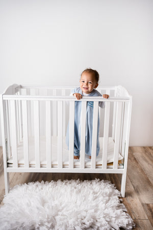 Baby standing in crib in Blue DreamSack Walker