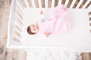Baby with feet in the air in Pink Magic DreamSack