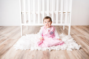 Baby sitting in front of crib in Pink Magic Dream Sack