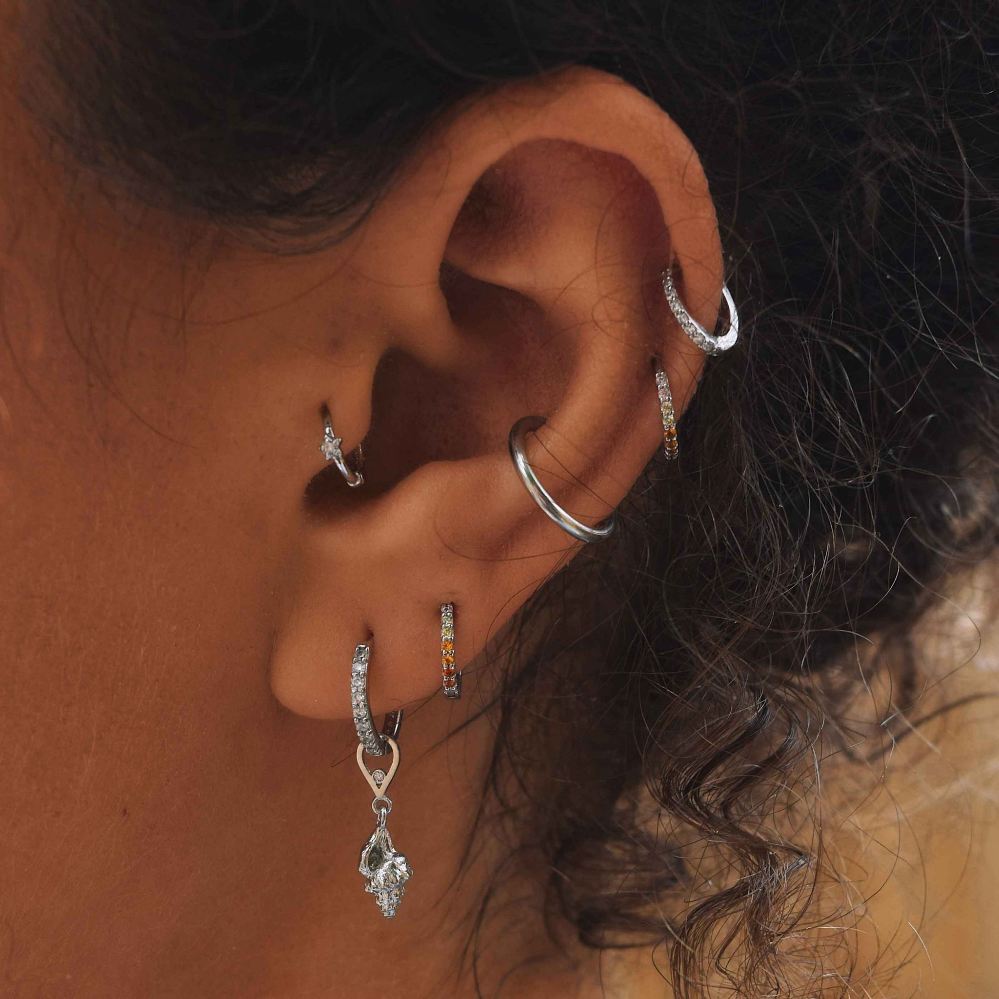 Light Rainbow Jewelled Huggies in Silver worn in second lobe and helix piercing