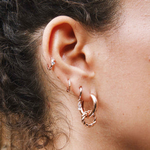 Baguette Stone Drop Huggies in Rose Gold worn with chunky hoops and jewelled huggies