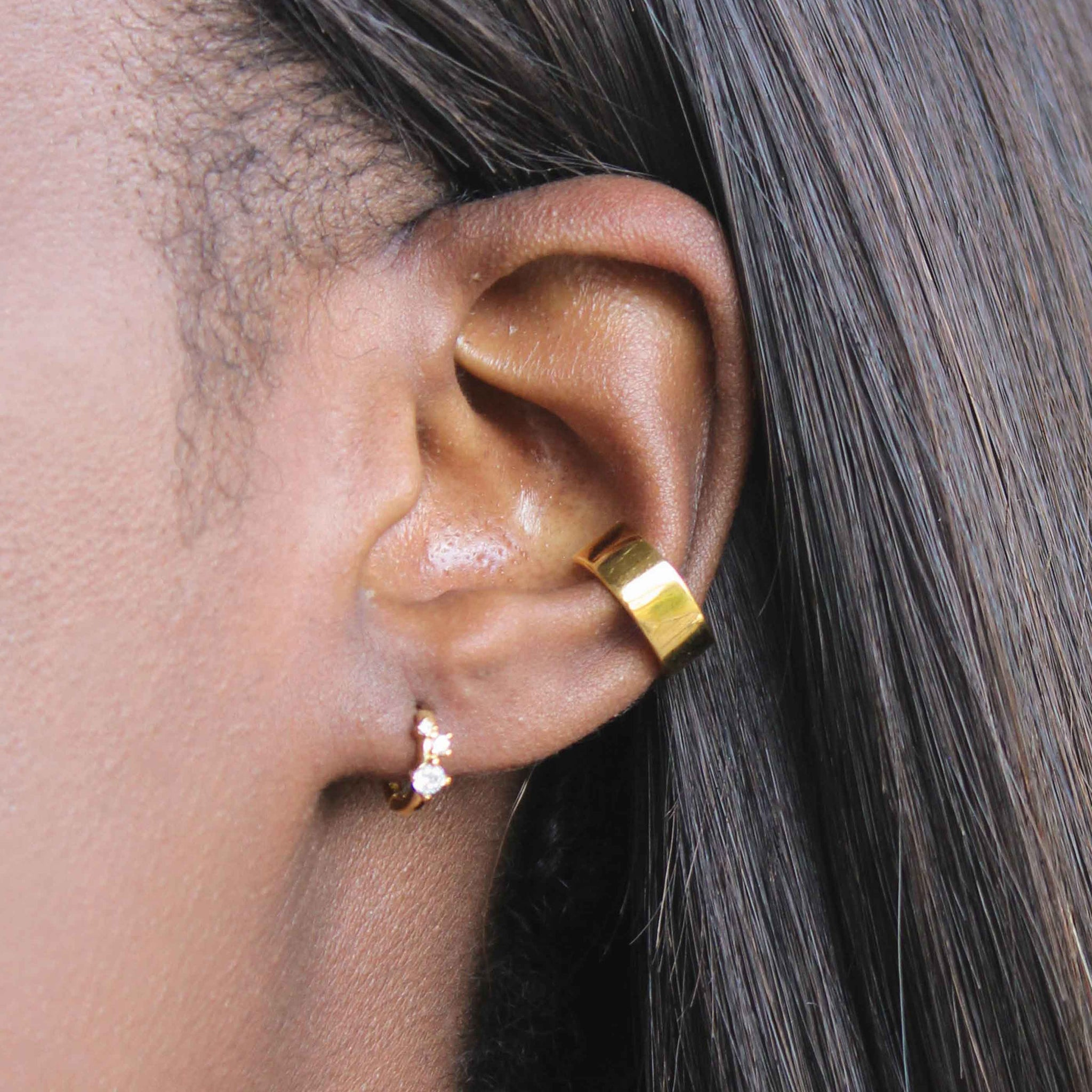 Triple Stone Huggies in Gold worn in first lobe piercing with boyfriend ear cuff