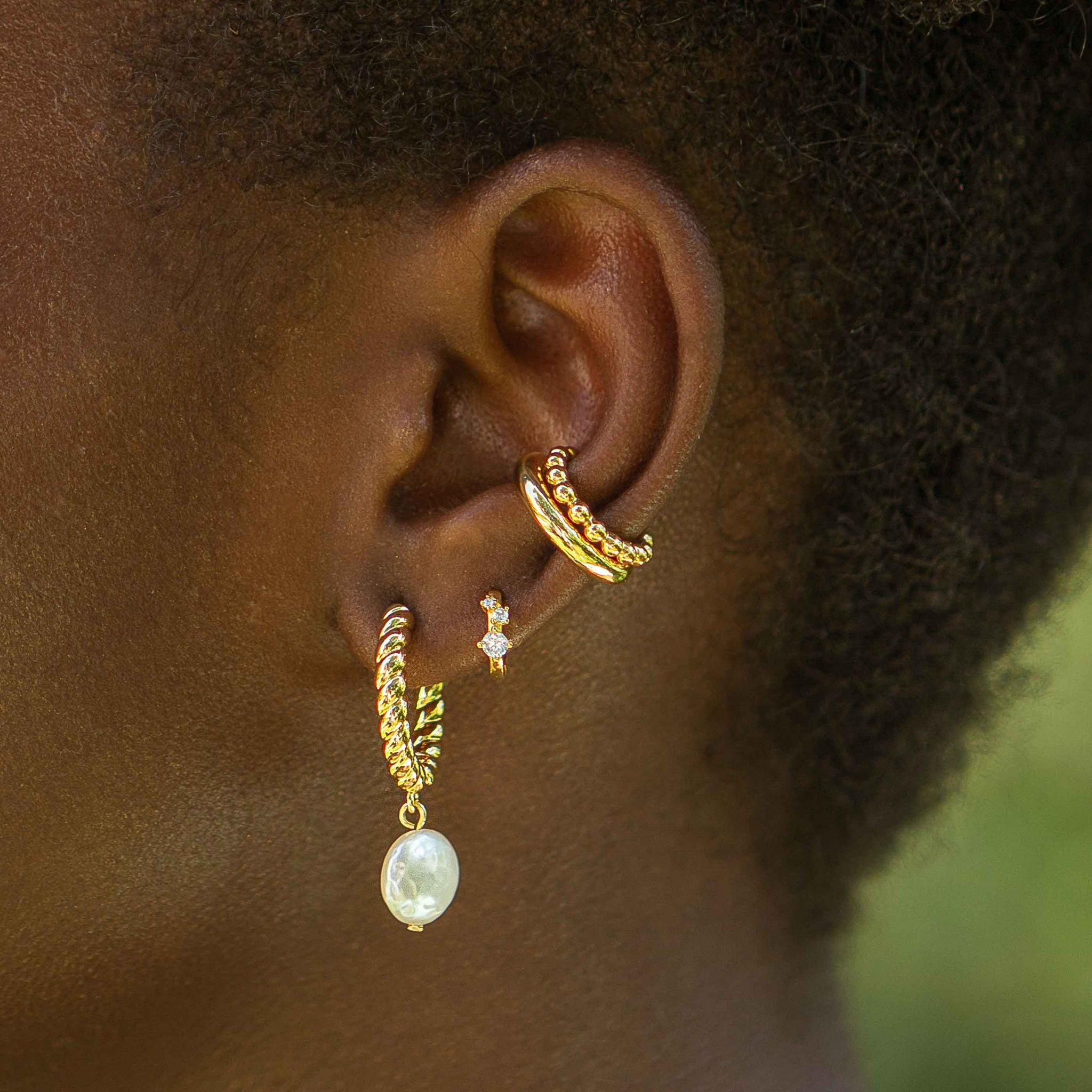 Triple Stone Huggies in Gold worn with pearl hoops and ear cuffs