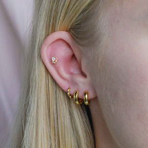 Bold Huggies in Gold worn in first and second lobe piercings