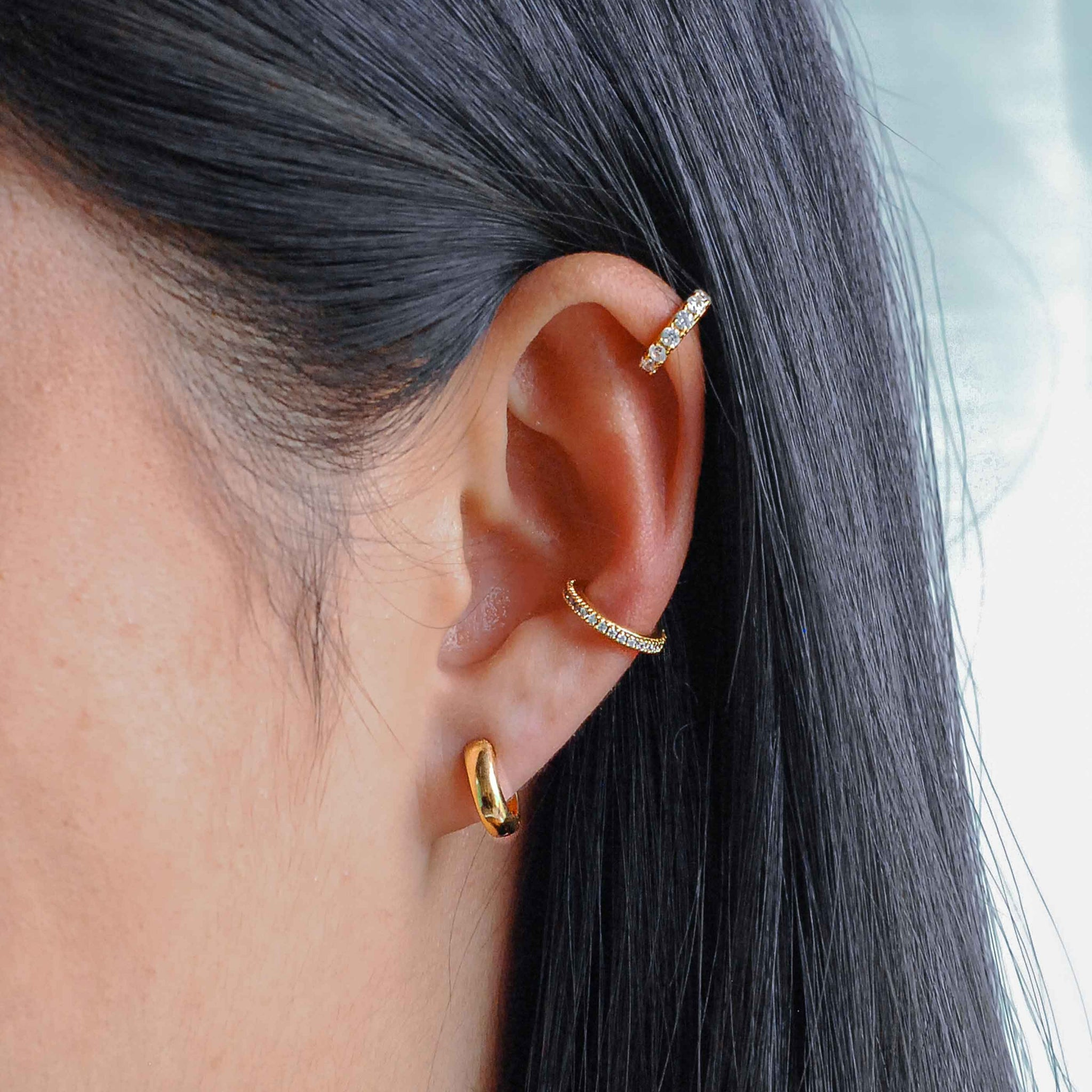 Model wearing Bold Huggies in Gold with jewelled ear cuffs