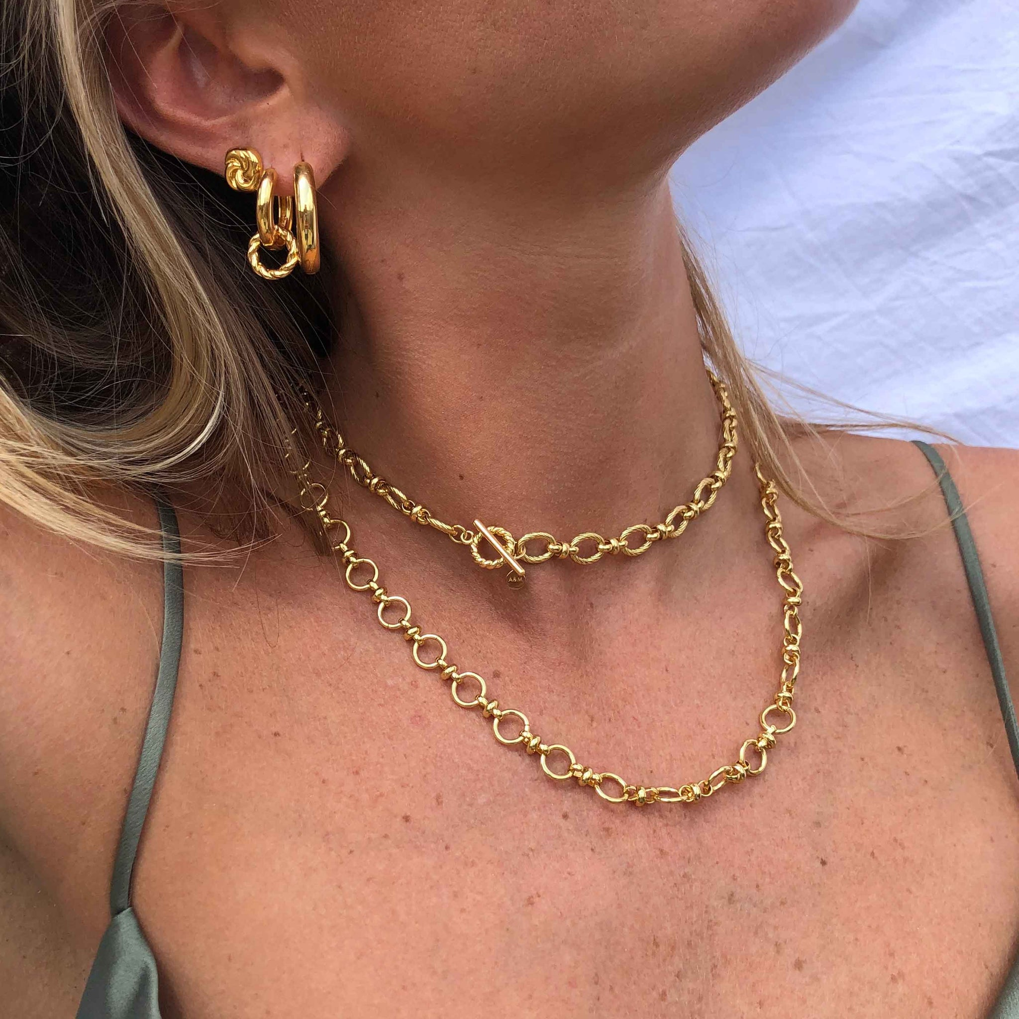 Model wearing gold chunky chain necklaces