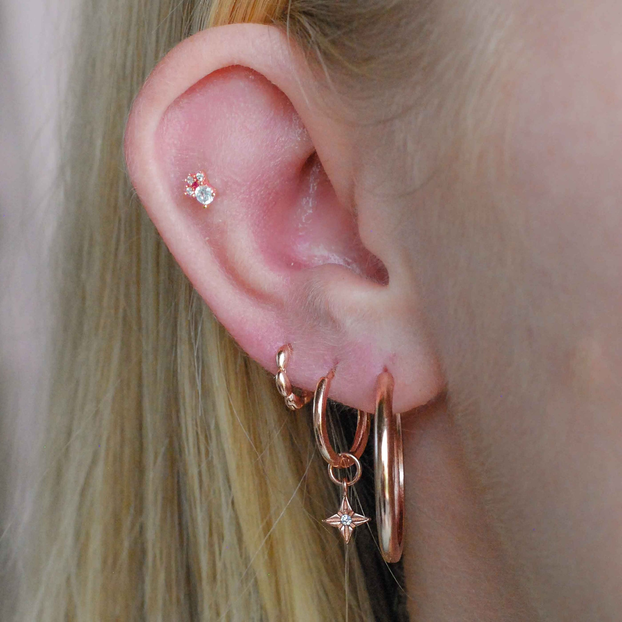Crystal & Triple Stone Barbell in Rose Gold worn in outer conch piercing