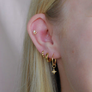 Etched Star Hoops in Gold worn with bold huggies and bubble clicker