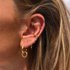 Mystic Jewelled Huggies in Gold worn in second lobe piercing with chunky hoops