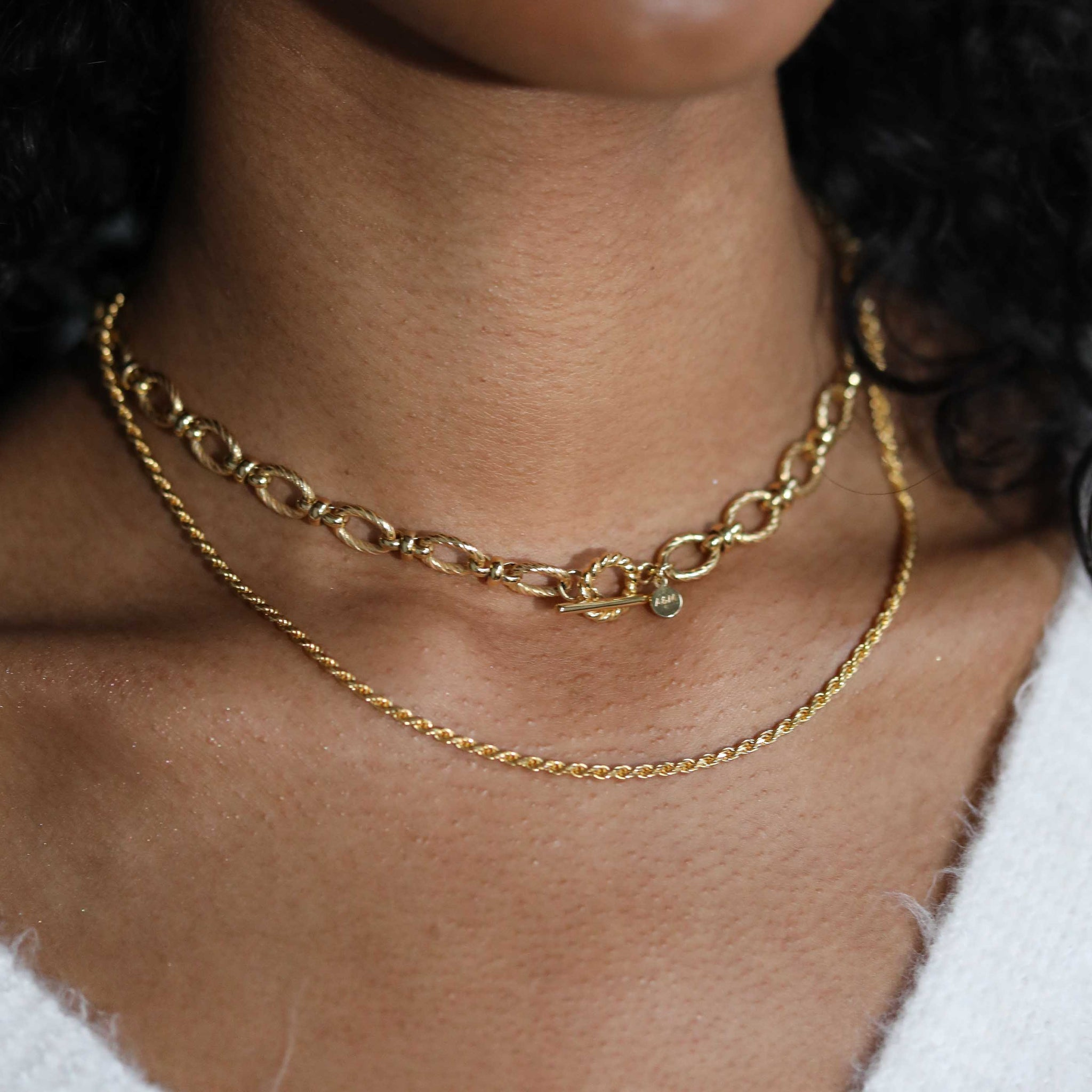 oval link t-bar necklace worn with rope chain necklace